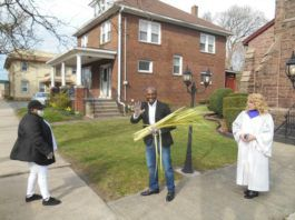 Pastor Adam McGahee, center, and his wife, Lisa, were giving out palm branches outdoors in front of Moving River Ministries, 439 S. Main St., Wilkes-Barre last year. The church's Praise Team will be handing them out again this year, from 10 a.m. to noon on March 28.                                  Mary Therese Biebel | Times Leader file photo