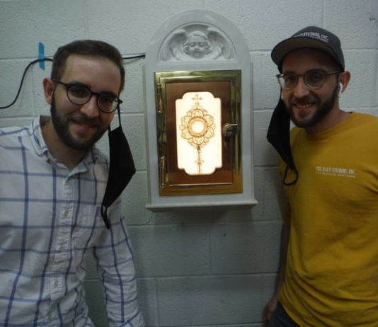 Twin brothers Peter Baut and James Baut, who represent a fourth generation of craftsmen to work at The Baut Studios in Swoyersville, pose near a recently completed reliquary that will be a resting place for a First Class Relic of St. John Paul II.                                  Mary Therese Biebel   Times Leader