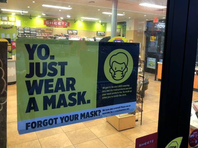 A mask policy poster is seen at the entrance to a Luzerne County Sheetz store on Friday evening. The Altoona-based chain is among those companies that say they will continue to require employees and customers to wear masks while reviewing the CDC's latest guidelines.                                  Roger DuPuis | Times Leader