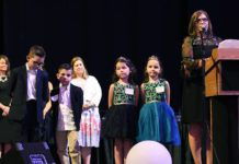 The 2021 EPIC Awards ATHENA recipient Kathi Bankes, podium, stands with four of her five grandchildren during her acceptance speech.                                  Tony Callaio | For Times Leader