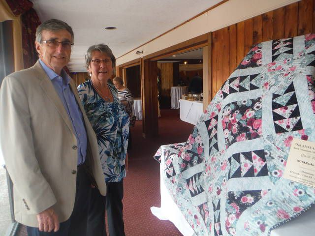 <p>Owen and Carol Lavery, of Shickshinny, admire a quilt made by Leslie Horoshko, which will be raffled off as a prize during the auction. The drawing for the quilt will take place on the final night of the auction, Aug. 15.</p>                                  <p>Mary Therese Biebel   Times Leader</p>