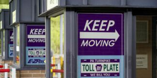 """Signs on the electronic toll booths indicate to motorists entering the Pennsylvania Turnpike in Gibsonia, Pa. on Monday, Aug. 30, 2021, to keep moving and the methods being used to collect tolls. More than $104 million in Pennsylvania Turnpike tolls went uncollected last year as the agency fully converted to all-electronic tolling. Turnpike records show the millions of motorists who don't use E-ZPass have a nearly 1 in 2 chance of riding without paying under the """"toll-by-plate"""" license plate reader system. (AP Photo/Keith Srakocic)"""